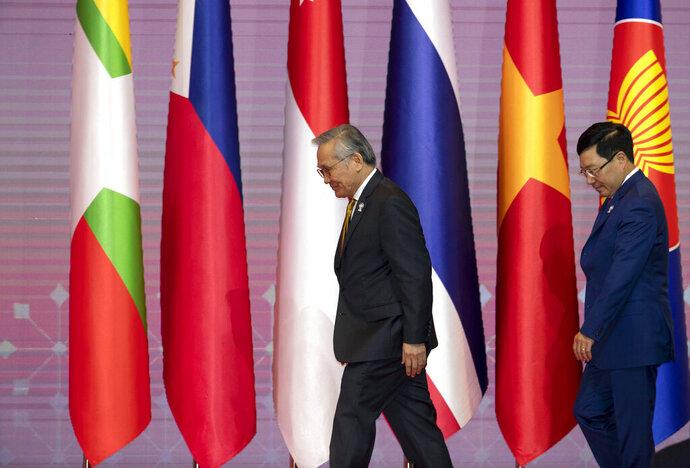 Thailand's Foreign Minister Don Pramudwinai, left, and Vietnam's Foreign Minister Pham Binh Minh walk for a group photo during the ASEAN Foreign Ministers' meeting in Bangkok, Thailand, Saturday, June 22, 2019. (AP Photo/Gemunu Amarasinghe)