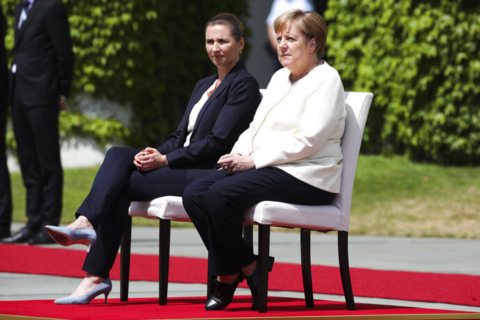 German Chancellor Angela Merkel, right, and Danish Prime Minister Mette Frederiksen, left, sit on chairs as they listen to the national anthems prior to a meeting at the chancellery in Berlin, Thursday, July 11, 2019. German Chancellor and the visiting Danish prime minister sit through their countries' national anthems at the welcoming ceremony in Berlin, a day after the latest of three incidents in which Merkel's body shook as she stood during similar events. (AP Photo/Markus Schreiber)