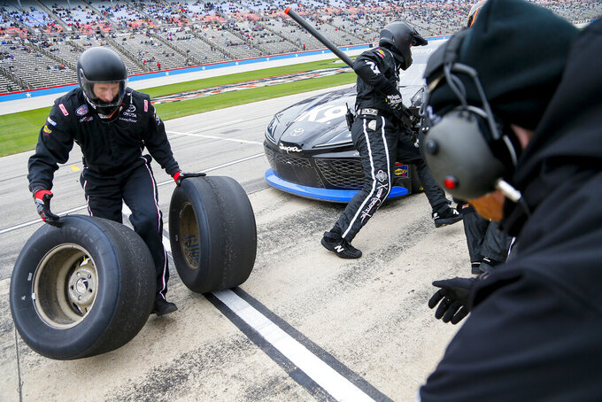 Members of Kyle Busch's pit crew change tires during a NASCAR auto race at Texas Motor Speedway, Saturday, March 30, 2019, in Fort Worth, Texas. (AP Photo/Brandon Wade)
