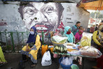 Indonesian women wearing masks as a precaution against the coronavirus outbreak sit at a food stall near a mural in Jakarta, Indonesia, Monday, Sept. 21, 2020. (AP Photo/Dita Alangkara)