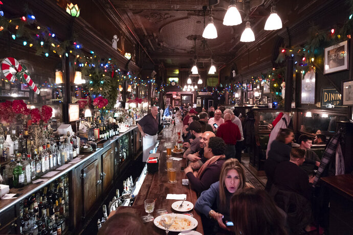 In this Dec. 27, 2019 photo, customers mingle in New York's Old Town Bar. Once a speakeasy during Prohibition, the Old Town Bar opened in 1892. In this era of bottomless mimosas, craft beers and ever-present happy hours, it's striking to recall that 100 years ago the United States imposed a nationwide ban on the production and sale of all types of alcohol. (AP Photo/Mark Lennihan)