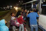 Migrants trying to reach the U.S. border board a public transport bus on the highway to Choloma, Honduras, Thursday, Jan. 14, 2021. About 200 Honduran migrants resumed walking toward the border with Guatemala early Thursday, a day before a migrant caravan was scheduled to depart San Pedro Sula.(AP Photo/Delmer Martinez)