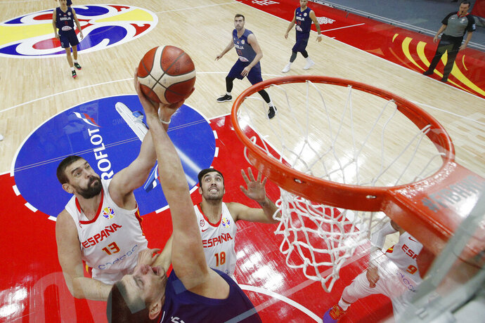 Marc Gasol of Spain is tackled by Nikola Jovic of Serbia as he attempt for a shot during their Group J second phase match for the FIBA Basketball World Cup, at the Wuhan Sports Center in Wuhan in central China's Hubei province, Sunday, Sept. 8, 2019. (AP Photo/Andy Wong. Pool)
