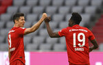 Munich's Robert Lewandowski, left, and team mate Alphonso Davies celebrate the fifth goal during the German Bundesliga soccer match between FC Bayern Munich and Fortuna Duesseldorf in Munich, Germany, Saturday, May 30, 2020. Because of the coronavirus outbreak all soccer matches of the German Bundesliga take place without spectators. (Christof Stache/Pool via AP)