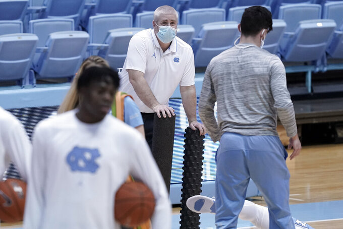 North Carolina trainer Doug Halverson, center, stands by while players warm up prior to an NCAA college basketball game against Syracuse in Chapel Hill, N.C., Tuesday, Jan. 12, 2021. The coronavirus pandemic has added another constantly shifting layer to what they do. The last 10 months have turned into a complicated juggling act of tending to athletes' day-to-day needs while dealing with the intricacies that come with trying to play sports and keeping everyone safe — themselves included — in a pandemic. (AP Photo/Gerry Broome)