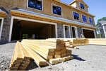 In this June 24, 2021 photo, lumber is piled at a housing construction site in Middleton, Mass.  Rising costs and shortages of building materials and labor are rippling across the homebuilding industry, which accounted for nearly 12% of all U.S. home sales in July. Construction delays are common, prompting many builders to pump the brakes on the number of new homes they put up for sale. As building a new home gets more expensive, some of those costs are passed along to buyers.  (AP Photo/Elise Amendola)