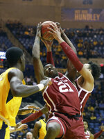 Oklahoma forward Kristian Doolittle (21) fights for control of a rebound during the first half of an NCAA college basketball game against West Virginia Saturday , Feb. 2, 2019, in Morgantown, W.Va. (AP Photo/Raymond Thompson)