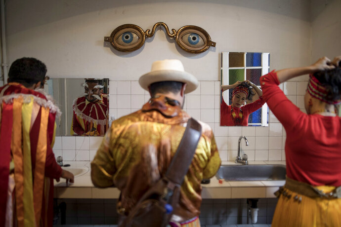 """Members of the Brazilian theater group Clowns of Shakespeare get ready for a performance in Bogota, Colombia, Saturday, Oct. 26, 2019. The troupe's play titled """"Abrazo,"""" or Hug, is among the growing list of shows, plays, conferences and other artistic projects that have been abruptly canceled in Brazil since the nation's President Jair Bolsonaro took office Jan. 1, after the troupe talked politics with the audience during the show's debut. (AP Photo/Ivan Valencia)"""