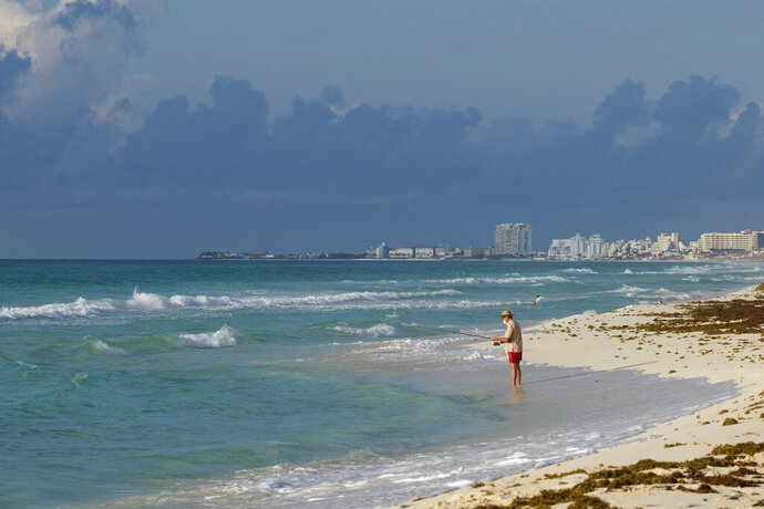 A tourist fishes from the shore in Cancun, Mexico, Thursday, June 11, 2020. An irony of the coronavirus pandemic is that the idyllic beach vacation in Mexico in the brochures really does exist now: the white sand beaches are sparkling clean and empty on the Caribbean coast. (AP Photo/Victor Ruiz)