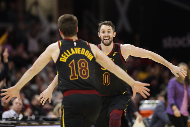 Cleveland Cavaliers' Kevin Love, right, and Matthew Dellavedova celebrate after Love made a three-point shot in overtime in an NBA basketball game against the San Antonio Spurs, Sunday, March 8, 2020, in Cleveland. The Cavaliers won 132-129 in overtime. (AP Photo/Tony Dejak)