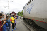 Onlookers wave as the Amtrak Vermonter passenger train arrives at the Montpelier station, in Berlin, Vt., on Monday July 19, 2021. A celebration was held at Amtrak stations across Vermont to mark the return of the passenger trains to Vermont for the first time since they were suspended at the beginning of the COVID-19 pandemic. (AP Photo/Wilson Ring)