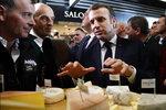 French President Emmanuel Macron eats cheese during a visit to the International Agriculture Fair (Salon de l'Agriculture) at the Porte de Versailles exhibition center in Paris, Saturday, Feb. 22, 2020. (AP Photo/Christophe Ena, Pool)