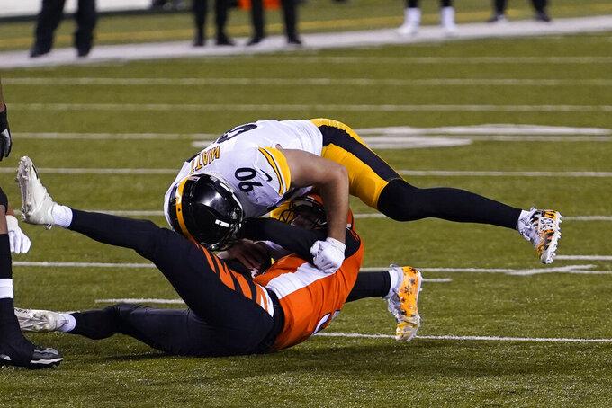 Cincinnati Bengals quarterback Ryan Finley (5) is sacked by Pittsburgh Steelers' T.J. Watt (90) during the first half of an NFL football game, Monday, Dec. 21, 2020, in Cincinnati. (AP Photo/Bryan Woolston)