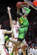 Oregon forward Kenny Wooten (14) jumps past Utah center Jayce Johnson (34) and shoots the ball during the first half of an NCAA college basketball game Thursday, Jan. 31, 2019, in Salt Lake City. (AP Photo/Chris Nicoll)