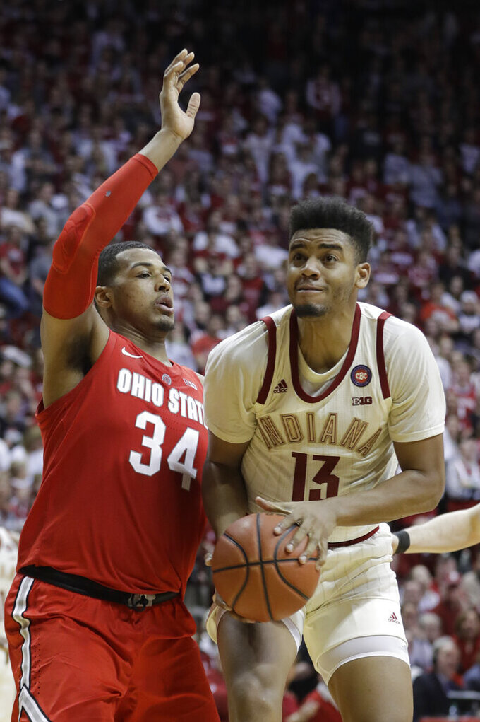 Indiana's Juwan Morgan (13) goes to the basket against Ohio State's Kaleb Wesson (34) during the second half of an NCAA college basketball game, Sunday, Feb. 10, 2019, in Bloomington, Ind. Ohio State won 55-52. (AP Photo/Darron Cummings)