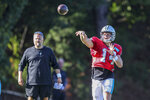 Carolina Panthers head coach Matt Rhule, left, watches quarterback Sam Darnold throw a pass during a joint practice with the Baltimore Ravens hosted by Carolina at the NFL football team's training camp in Spartanburg, S.C., Wednesday, Aug. 18, 2021. (AP Photo/Nell Redmond)