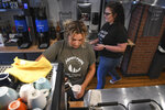 Teen worker Courtney Collins, 19, pours a drink as Elizabeth Bonifati walks behind her at Harvest Moon Coffee & Chocolates in Tarentum on Friday, July 16, 2021. (Kristina Serafini/Pittsburgh Tribune-Review via AP)
