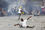 In this Oct. 4, 2019 photo, a protestor drops to the ground as he pleads with police after they fired tear gas to prevent protestors from marching toward the United Nations headquarters in Port-au-Prince, Haiti. Thousands of protesters marched through the Haitian capital to the U.N. headquarters Friday in one of the largest demonstrations in a weeklong push to oust the embattled President Jovenel Moise. (AP Photo/Rebecca Blackwell)