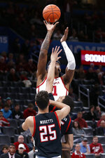 Oklahoma forward Kristian Doolittle, rear, shoots over Texas Tech guard Davide Moretti (25) and guard Kevin McCullar, center, in the first half of an NCAA college basketball game Tuesday, Feb. 25, 2020, in Oklahoma City. (AP Photo/Sue Ogrocki)