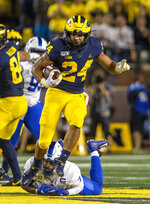 Michigan running back Zach Charbonnet (24) avoids Middle Tennessee safety Jovante Moffatt (7) to rush 40 yards during the fourth quarter of an NCAA football game in Ann Arbor, Mich., Saturday, Aug. 31, 2019. Michigan won 40-21. (AP Photo/Tony Ding)