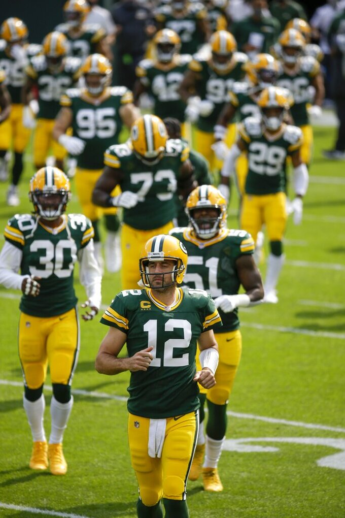 Green Bay Packers' Aaron Rodgers runs on the field with teammates before an NFL football game against the Detroit Lions Sunday, Sept. 20, 2020, in Green Bay, Wis. (AP Photo/Mike Roemer)