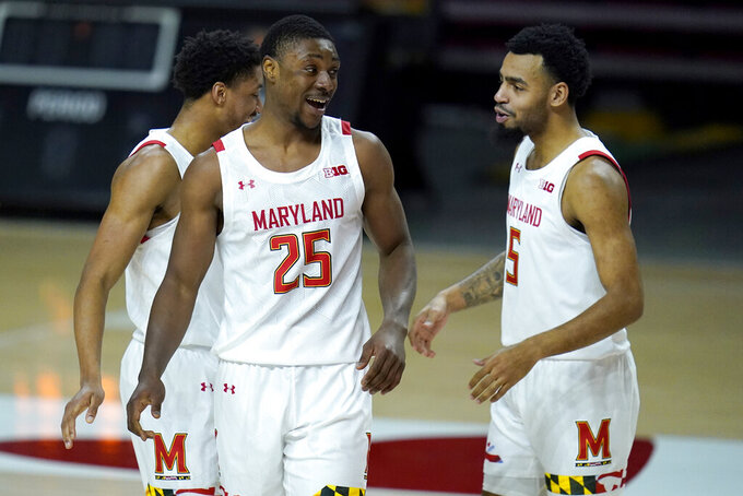 Maryland forward Jairus Hamilton (25) reacts with teammates Aaron Wiggins, left, and Eric Ayala after a play against Nebraska during the second half of an NCAA college basketball game, Wednesday, Feb. 17, 2021, in College Park, Md. (AP Photo/Julio Cortez)