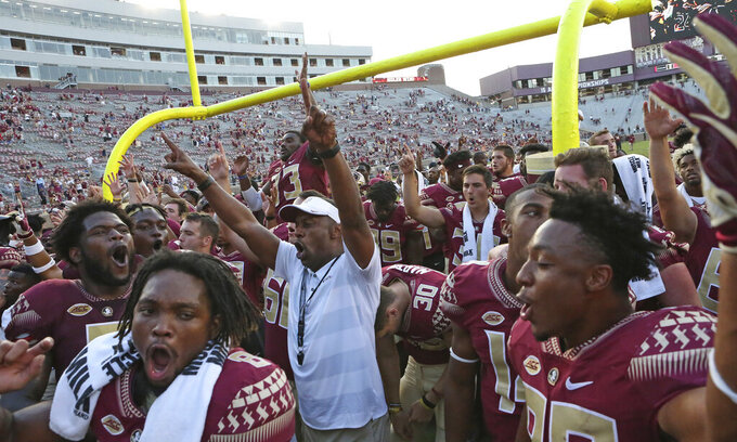 FILE - In this Sept. 22, 2018 file photo Florida State head coach Willie Taggart, center, celebrates a win with his team at the end of an NCAA college football game against Northern Illinois in Tallahassee Fla. Decades of Florida State football dominance is displayed on the walls just outside of Taggart's office. Trophies and plaques commemorate All-America players and championship teams. Lots of them. Taggart takes responsibility for last year's 5-7 finish, but remains confident in his plan to get Florida State back on track because it has worked before. (AP Photo/Steve Cannon, file)