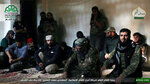 FILE - This file photo posted, Sunday, Oct. 30, 2016, by the Syrian militant group Ahrar al-Sham, shows the general commander of Ahrar al-Sham, Mohannad al-Masri, center, visiting fighters in rural western Aleppo, Syria. As the world attention is focused on the government offensive on rebel-held eastern suburbs of Damascus known as eastern Ghouta, the grinding war has been ongoing for two weeks in Idlib and Aleppo provinces killing scores of people many of them fighters. Arabic reads,