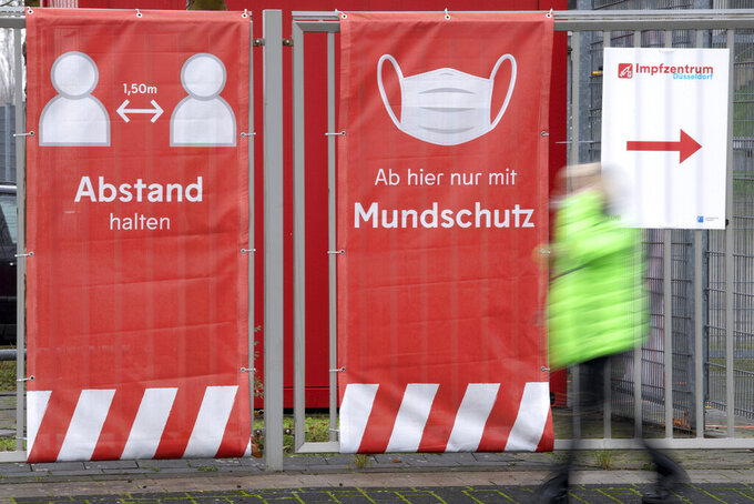 A person walks past an information sign for a vaccination center at a soccer stadium, home of German second division team Fortuna Duesseldorf, in Duesseldorf, Germany, Tuesday, Dec. 1, 2020. The German government is preparing to roll out a nationwide coronavirus vaccination program. (Federico Gambarini/dpa via AP)