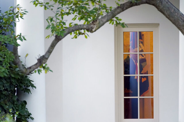 President Donald Trump waves to members of the press from the Oval Office at the White House in Washington, Tuesday, Oct. 20, 2020. (AP Photo/Andrew Harnik)