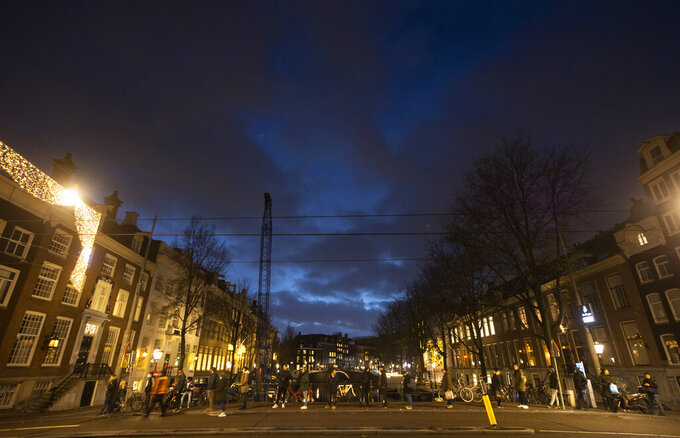 """People queue on a bridge to buy pot at a nearby coffeeshop after being directed by a security guard, left in orange vest, in Amsterdam, Netherlands, Monday, Dec. 14, 2020. Dutch Prime Minister Mark Rutte is expected to impose a tough lockdown Monday night in a speech to the nation as coronavirus infection rates in the Netherlands rise sharply despite a two-month """"partial lockdown."""" Dutch media citing unnamed government sources said Rutte will likely order schools to close from Wednesday, and shut non-essential shops and businesses such as hair salons, museums and theaters from Tuesday until Jan. 19, 2021. (AP Photo/Peter Dejong)"""