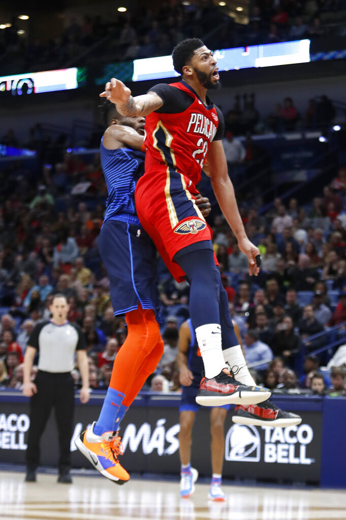 New Orleans Pelicans forward Anthony Davis (23) collides with Oklahoma City Thunder forward Nerlens Noel (3) after attempting to block a shot at the end of the first half of an NBA basketball game in New Orleans, Thursday, Feb. 14, 2019. Davis kept his left arm still as he walked to the locker room shortly after fouling Noel on an attempted shot block with his left hand. When the second half began, the Pelicans announced that Davis was out of the remainder of the game with a left shoulder injury, The Pelicans won 131-122. (AP Photo/Tyler Kaufman)