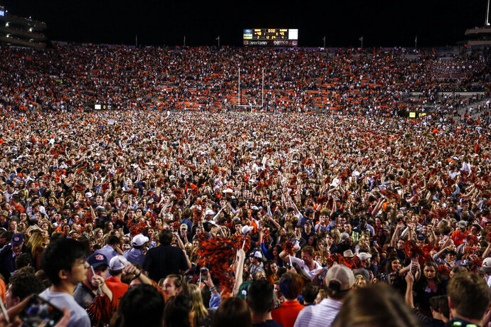 Auburn fans storm the field after they defeated Alabama 48-45 in an NCAA college football game Saturday, Nov. 30, 2019, in Auburn, Ala. (AP Photo/Butch Dill)