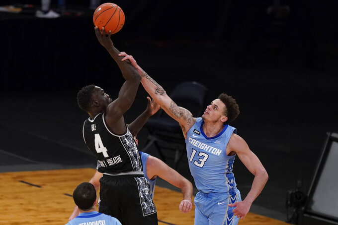 Georgetown's Chudier Bile (4) shoots over Creighton's Christian Bishop (13) during the second half of an NCAA college basketball game in the championship of the Big East Conference tournament Saturday, March 13, 2021, in New York. (AP Photo/Frank Franklin II)