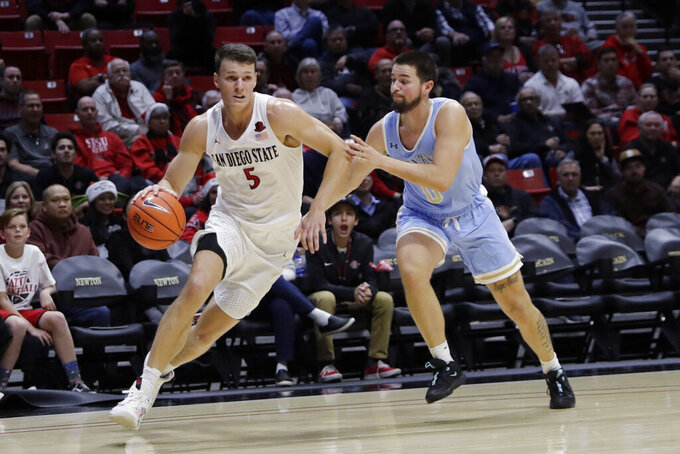 San Diego State's Yanni Wetzell drives to the basket as San Diego Christian's Keshad Johnson defends during the first half of an NCAA college basketball game Wednesday, Dec. 18, 2019, in San Diego. (AP Photo/Gregory Bull)