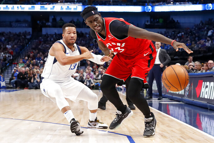 Dallas Mavericks guard Jalen Brunson (13) defends as Toronto Raptors forward Pascal Siakam (43) reaches out to control the ball in the first half of an NBA basketball game in Dallas, Saturday, Nov. 16, 2019. (AP Photo/Tony Gutierrez)