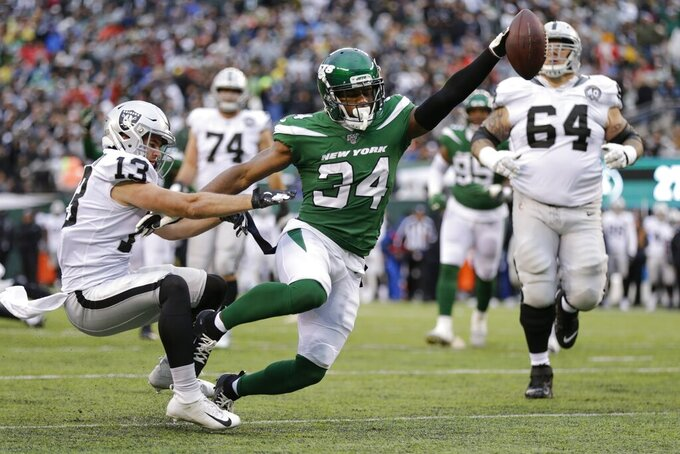 New York Jets' Brian Poole (34) breaks a tackle by Oakland Raiders' Hunter Renfrow (13) to score a touchdown after intercepting a pass during the second half of an NFL football game Sunday, Nov. 24, 2019, in East Rutherford, N.J. (AP Photo/Adam Hunger)