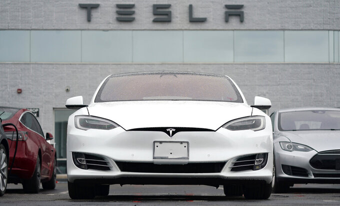 FILE - This Sunday, May 9, 2021 file photo shows vehicles at a Tesla location in Littleton, Colo. According to the U.S. National Transportation Safety Board, home security camera footage shows that the owner of a Tesla got into the driver's seat of the car shortly before a deadly crash in suburban Houston. But the preliminary report on the crash that killed two men doesn't explain why police found no one behind the wheel of the car, which burst into flames after crashing about 550 feet (170 meters) from the owner's home. (AP Photo/David Zalubowski)