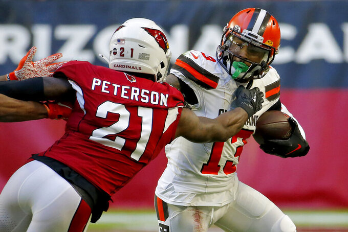 Cleveland Browns wide receiver Odell Beckham (13) tries to elude the tackle of Arizona Cardinals cornerback Patrick Peterson (21) during the second half of an NFL football game, Sunday, Dec. 15, 2019, in Glendale, Ariz. (AP Photo/Rick Scuteri)