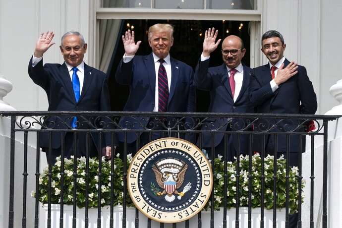 FILE - In this Tuesday, Sept. 15, 2020 file photo, Israeli Prime Minister Benjamin Netanyahu, left, U.S. President Donald Trump, Bahrain Foreign Minister Khalid bin Ahmed Al Khalifa and United Arab Emirates Foreign Minister Abdullah bin Zayed al-Nahyan pose for a photo on the Blue Room Balcony after signing the Abraham Accords during a ceremony on the South Lawn of the White House in Washington. Saudi Arabia insists officially that there can be no formal ties with Israel before Palestinian statehood is achieved, but state-backed media and clerics have softened their tone toward Jews and there has been no official condemnation or criticism of the deals signed by the UAE or Bahrain with Israel. (AP Photo/Alex Brandon, File)