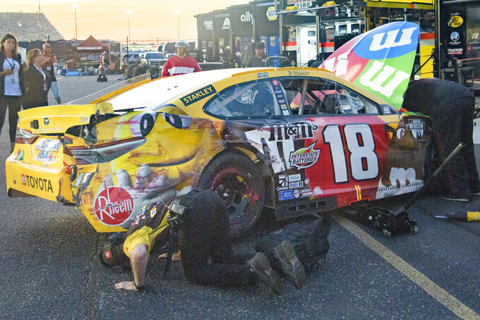 A car is looked over by crew after Kyle Busch pulled out of the pit area and parked next to his team's hauler during a NASCAR Cup Series auto race Sunday, Sept. 5, 2021, in Darlington, S.C. (AP Photo/John Amis)