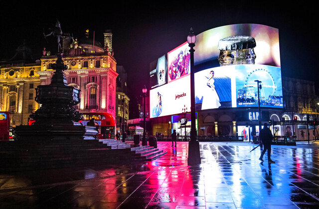 A man walks across the normally busy Piccadilly Circus in central London after a heavy rain downpour, Monday Nov. 9, 2020.  The London streets are nearly deserted during the first full week of a four-week coronavirus lockdown in England, but some are calling to allow businesses to reopen their doors to kickstart the city economy. (Victoria Jones/PA via AP)