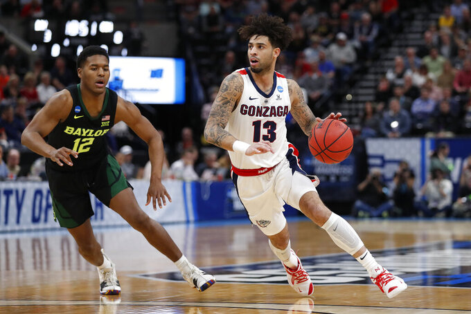 Gonzaga guard Josh Perkins (13) drives to the hoop past Baylor guard Jared Butler (12) during the first half of a second-round game in the NCAA men's college basketball tournament Saturday, March 23, 2019, in Salt Lake City. (AP Photo/Jeff Swinger)