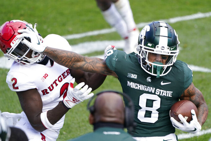 Michigan State wide receiver Jalen Nailor (8) stiff arms Rutgers defensive back Avery Young (2) during the second half of an NCAA college football game, Saturday, Oct. 24, 2020, in East Lansing, Mich. (AP Photo/Carlos Osorio)