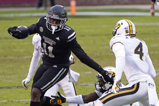 Mississippi State wide receiver Geor'quarius Spivey (11) tries to evade Missouri safety Jalani Williams (4) after catching a pass during the first half of an NCAA college football game, Saturday, Dec. 19, 2019, in Starkville, Miss. (AP Photo/Rogelio V. Solis)