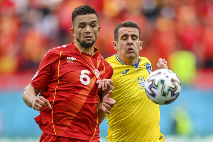 North Macedonia's Visar Musliu, left, duels for the ball with Ukraine's Artem Besyedin during the Euro 2020 soccer championship group C match between Ukraine and North Macedonia at the National Arena stadium in Bucharest, Romania, Thursday, June 17, 2021. (Justin Setterfield, Pool via AP)