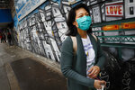Dr. Jeanie Tse, chief medical officer at the Institute for Community Living, walks along a graffiti mural during her rounds treating psychiatric patients, Wednesday, May 6, 2020, in the Brooklyn borough of New York. (AP Photo/John Minchillo)