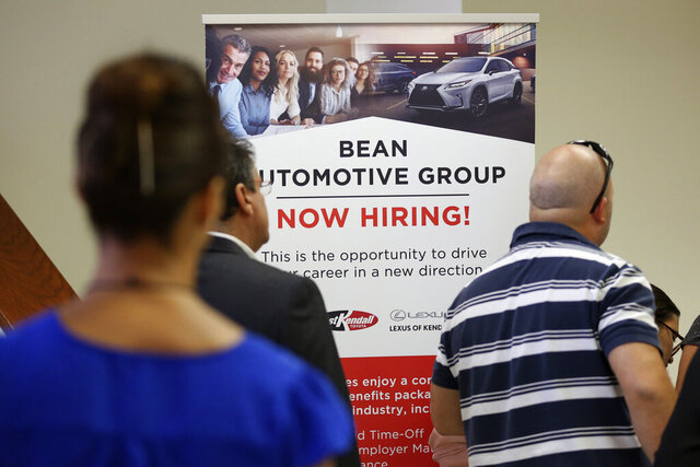 FILE - In this Sept. 18, 2019, file photo people stand in line to inquire about jobs available at the Bean Automotive Group during a job fair in Miami. On Friday, Jan. 10, 2020, the U.S. government issues the December jobs report. (AP Photo/Lynne Sladky, File)