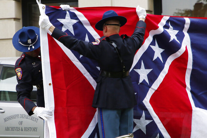 A Mississippi Highway Safety Patrol honor guard carefully folds the retired Mississippi state flag after it was raised over the Capitol grounds one final time in Jackson, Miss., Wednesday, July 1, 2020. The banner was the last state flag with the Confederate battle emblem on it. (AP Photo/Rogelio V. Solis)