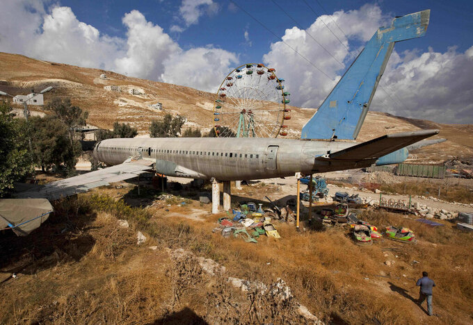 """FILE - In this Oct. 6, 2009 file photo, an old Boeing 707 awaits conversion to a restaurant and cafe, near the west bank town of Nablus. The territory has no civilian airport and those who can afford a plane ticket must catch their flights in neighboring Jordan. After a quarter century of effort, twins brothers, Khamis al-Sairafi and Ata, opened """"The Palestinian-Jordanian Airline Restaurant and Coffee Shop al-Sairafi"""" on July 21, 2021, offering people an old airplane for customers to board. (AP Photo/Oded Balilty, File)"""